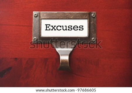 Lustrous Wooden Cabinet with Excuses File Label in Dramatic LIght. - stock photo
