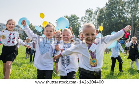 Lutsk. Ukraine. September 1, 2018; Children go to school in the first class. Holiday knowledge. Launch yellow and blue balloons into the sky. #1426204400