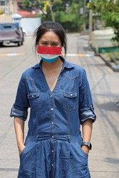 Luxembourg flag on hygienic mask. Masked woman prevent germs and wear denim skirt dress. Tiny Particle or virus corona or Covid 19 protection. Concept of Combating illness.