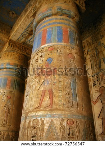 Luxor: polychromed columns with carvings of the pharaoh and his wife surrounded by hieroglyphs, in Medinet Habu temple, dedicated to Ramesses III. Luxor, Egypt
