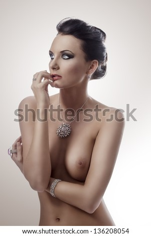 luxuriant nude woman in topless and brown hair posing on white background with some brilliant jewelery