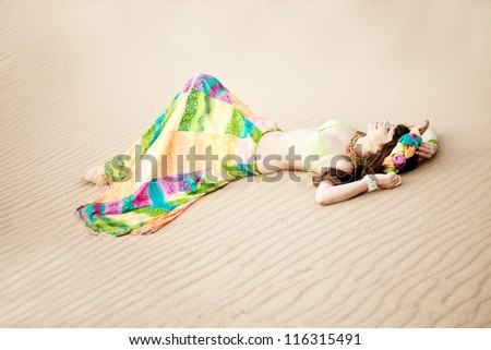 Luxurious beautiful fashionable woman on the beach at sun