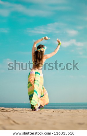 Luxurious beautiful fashionable woman on the beach at sun