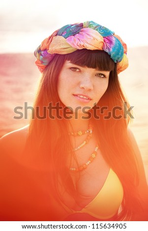 Luxurious beautiful fashionable woman on the beach at sunset