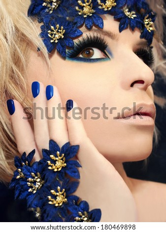 Luxurious blue makeup and manicures on the girl with blond hair and decorative flowers on her head.