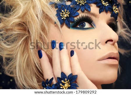 Luxurious blue manicure and makeup on a girl with blond hair and decorative flowers on a dark background.