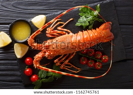 Luxurious boiled spiny lobster surrounded by fresh tomatoes, lemon, herbs and melted butter close-up on a black stone. horizontal top view from above #1162745761