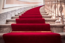 Luxurious building interior with the marble stairs covered with a red carpet