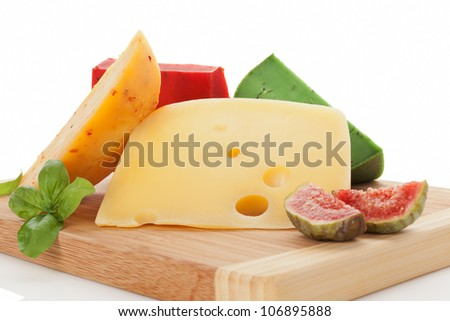 Luxurious cheese still life. Red, green and yellow gouda, swiss cheese emmentaler with fresh basil leaves and tropical fruit fig on wooden chopping board.