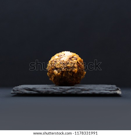 Luxurious chocolate truffle, round candy with waffle crumbs, on a stone stand on a black background