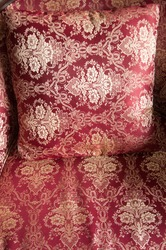 luxurious cushions on bed in gold brocade, red textiles