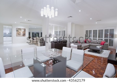 Luxurious dining room with living rooms and kitchen in the background - stock photo