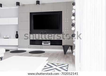 Luxurious entertainment zone with big TV screen in modern monochromatic apartment #702052141