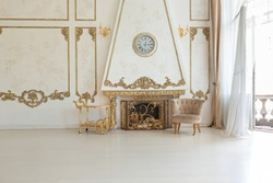 luxurious expensive interior of a large baroque royal living room. antique furniture, gold trim, huge windows, fireplace with gold stucco on the walls. full of daylight