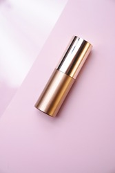 Luxurious golden cosmetic tube bottle on pink and white backdrop. Minimalism product still life from above. Beauty blogging, glamour, shop, studio light. Geometric, close up