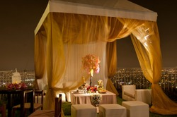 Luxurious hill top garden party at night with gold fabric gazebo, lavishly decorated inside with floral bouquets and candles.