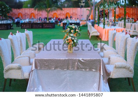 luxurious Long dinner tables and chairs, rich decorated with flower pots, Indian Wedding setup - Image