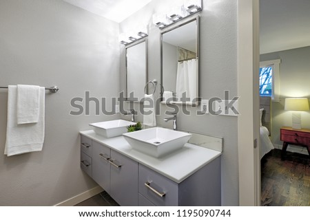 Luxurious master bathroom with blue vanity cabinet and two square vessel sinks. #1195090744
