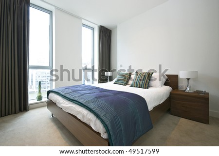 Luxurious modern bedroom with double bed, built in wardrobe and decorative bedding