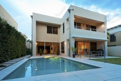 Luxurious modern house with swimming pool and backyard at sunset