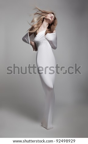 Luxurious mystical young Woman in White clothes with Waving Long Hair gracefully posing in studio. Advertisement Sales concept. Poster Art Design