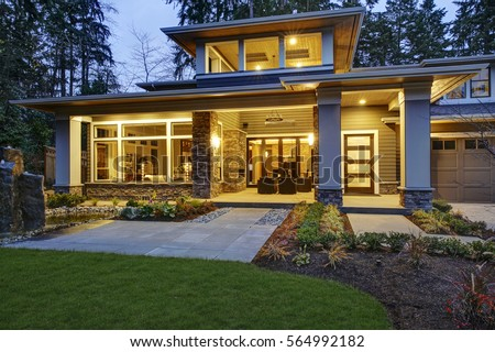 Luxurious new construction home exterior with front patio and column porch. Outdoor living space boasts taupe wicker chairs facing a stone outdoor fireplace. Northwest, USA  #564992182