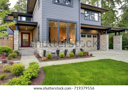 Luxurious new home with curb appeal. Trendy grey two-story exterior in Bellevue with large picture windows, stone foundation veneer, covered porch and concrete pathway. Northwest, USA #719379556