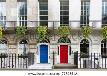 Luxurious old town house with a white facade and blue and red doors, London, UK