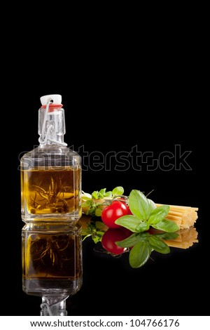 Luxurious pasta background. Spaghetti, tomatoes, basil and olive oil isolated on black background. Culinary cooking.