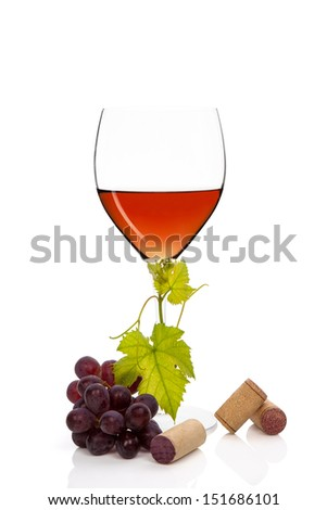Luxurious rose wine in wine glass with red grapes, vine leaves and wine corks isolated on white background. Culinary exclusive wine.