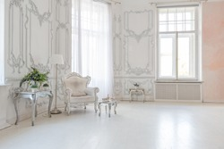 luxurious royal interior of the sitting room, light walls decorated with stucco molding, expensive chandelier on the ceiling, the furniture is very beautiful, silver and white and large windows