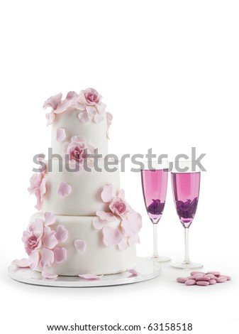 Luxurious wedding cake with flowers and two champagne flute glasses with cocktails; isolated white studio background with copy space.