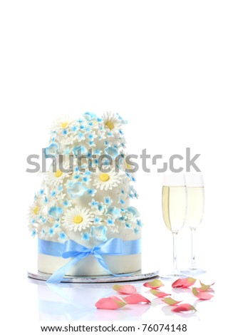 Luxurious wedding cake with flowers and two champagne flute glasses with rose petals; white studio background with copy space.