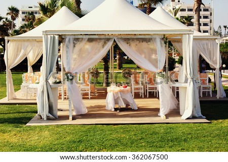 Luxurious wedding tent with haze peachy fabric and floral decorations near the palm trees and blue ocean