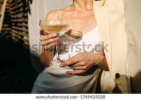 Luxurious woman wearing a white dress, holding a coupe with champagne in sun light. Concept of an open air party. Photo stock ©