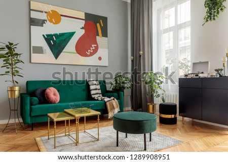 Luxury and modern home interior with design green sofa, navy commode, tables, pouf and accessroies. A lot of plants in the room. Abstract painting.  Stylish decor of living room with brown parquet.