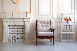 Luxury apartment suite lounge. Wooden beige armchair stands next to fireplace. Cozy interior