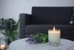 luxury aroma lighting aromatic scented candle glass displayed on the white marble table with bouquet of flowers to creat romantic and relax ambient with background of grey sofa in living room