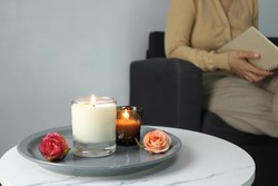 luxury aroma lighting aromatic scented candle glass displayed on white marble table with rose flowers to creat relax ambient with background of a woman sitting and reading on grey sofa in living room