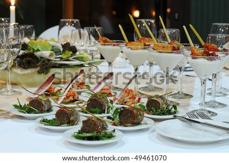 Luxury banquet table setting in restaurant. Table with the wineglasses, snacks and cocktails.