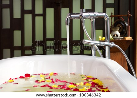 Luxury bath tub with water and flowers