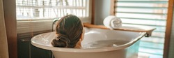 Luxury bath woman relaxing in hot bathtub in hotel resort suite room enjoying pampering spa moment lifestyle banner panorama.