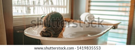 Luxury bath woman relaxing in hot bathtub in hotel resort suite room enjoying pampering spa moment lifestyle banner panorama. Foto stock ©