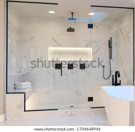 Luxury bathroom interior with tub, shower shelve and walk in shower. white marble and dark brown brass faucet.