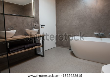 Luxury bathroom with polished concrete on the walls and PVC on the floor Stockfoto ©