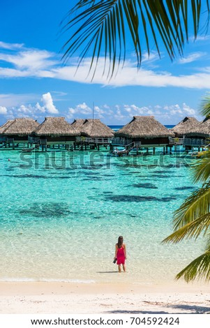 Luxury beach travel vacation woman in Tahiti. Tourist enjoying ocean water at overwater bungalow hotel villas in French Polynesia, Moorea island in south pacific, famous getaway destination. #704592424