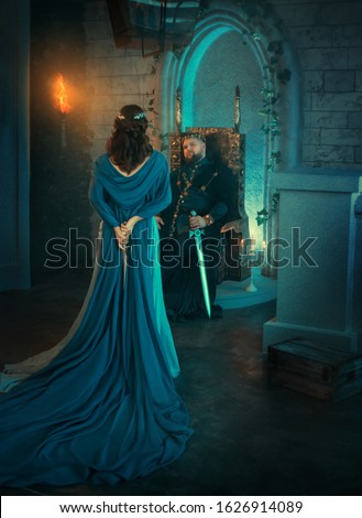 Luxury beauty Queen turned away. medieval royal creative clothes. Lady holds gothic dagger back. Blue cloak cape. Backdrop old retro room. Strong adult men king sits on throne. Dangerous conspirator Сток-фото ©