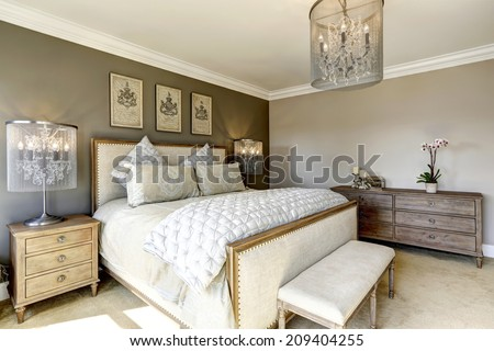 Photo of Luxury bedroom interior with carved wood bed, dresser and nightstands