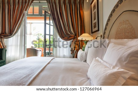Luxury bedroom that opens with French doors onto a terrace.  King bed with white linens and pillows.