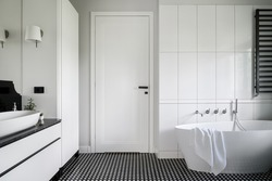 Luxury black and white bathroom with freestanding bathtub, stylish mosaic tile floor and white doors with black handle